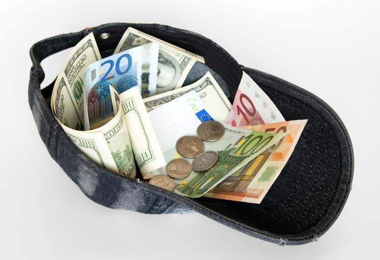 Kšiltovka plná peněz, bankovek a mincí.